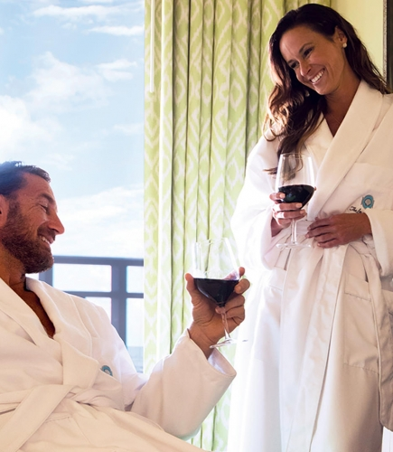 couple drink wine in bathrobes by a roaring fire