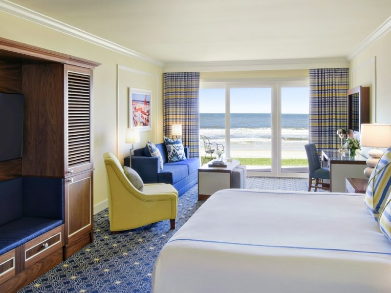 A hotel room featuring a king bed with white linens, and upholstered blue headboard. In the background, a desk and sitting area look out onto the beach beyond.
