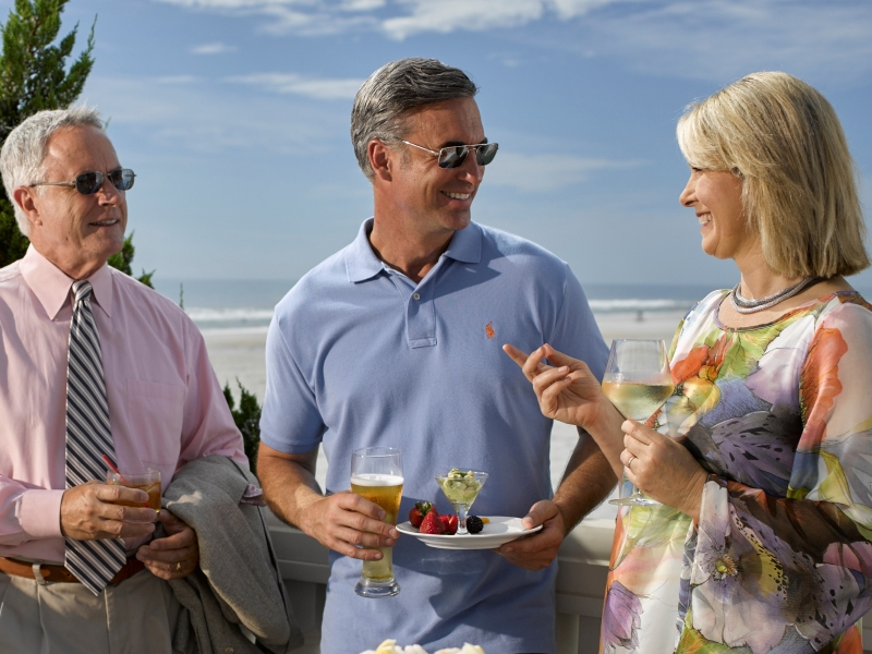 Two middle aged men and a middle aged woman drink cocktails and eat hors d'oeuvres with the beach in the background.