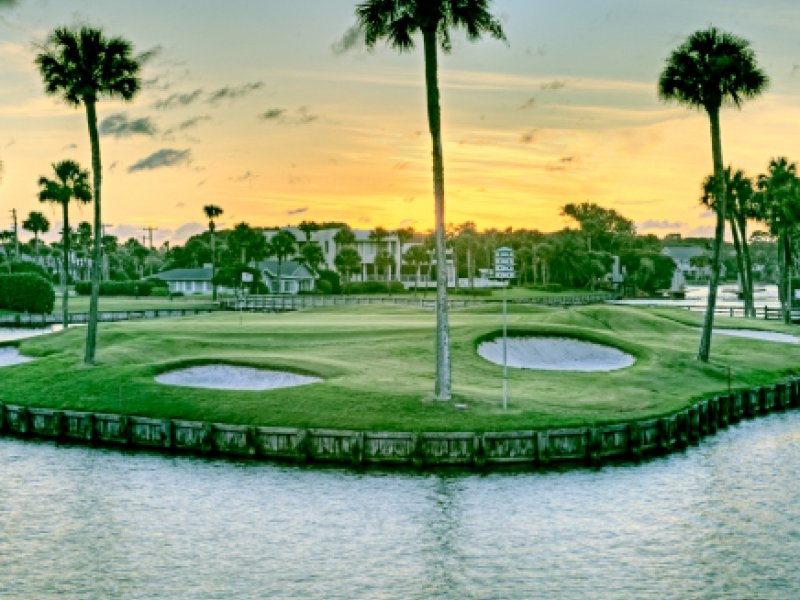 A view of the Lagoon Course at Ponte Vedra Inn & Club with lagoon in foreground, with bunkers and palm trees at sunset.