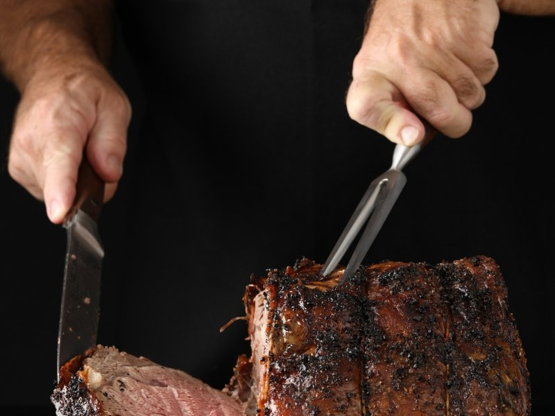 Man cutting prime rib