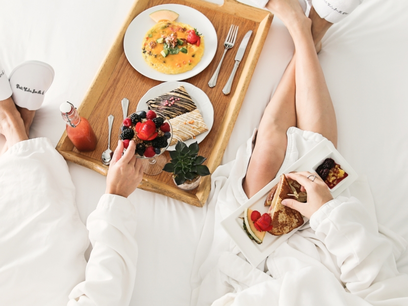 two women in bathrobes eating breakfast