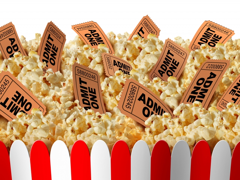 A red and white box holds popcorn, with paper movie stub tickets poking out from the popcorn.
