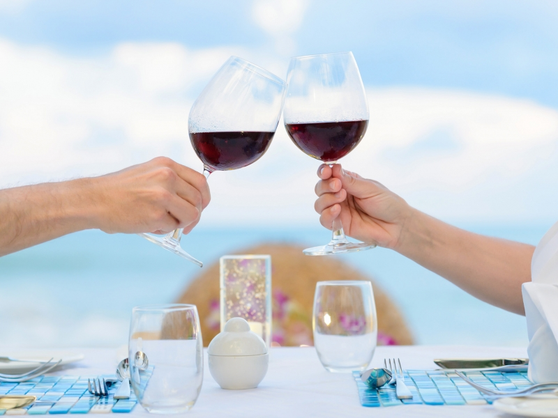 Two hands raise glasses of red wine over a table with the ocean in the background.