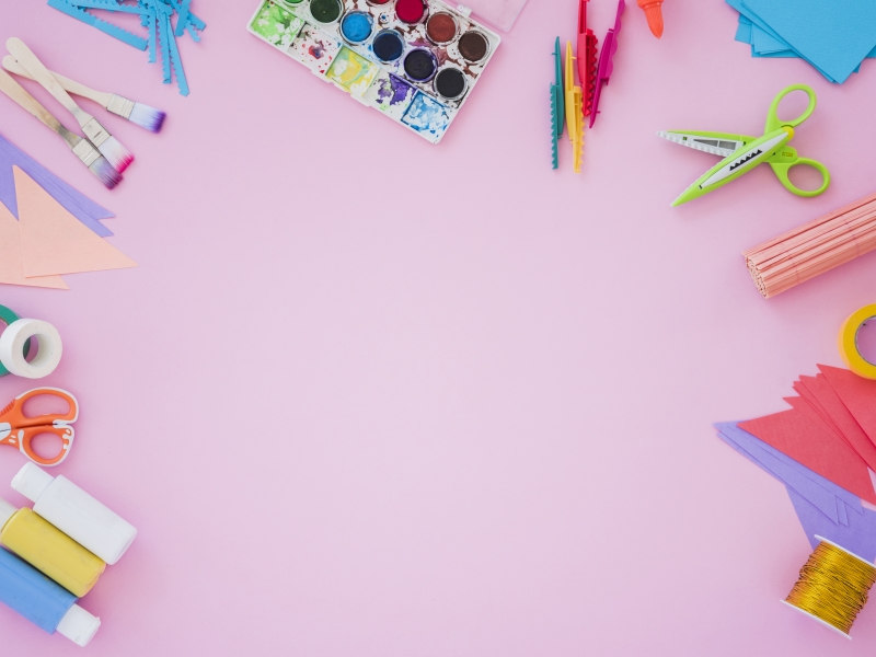 Paint brushes, scissors, and paper craft supplies lie on a pink background.