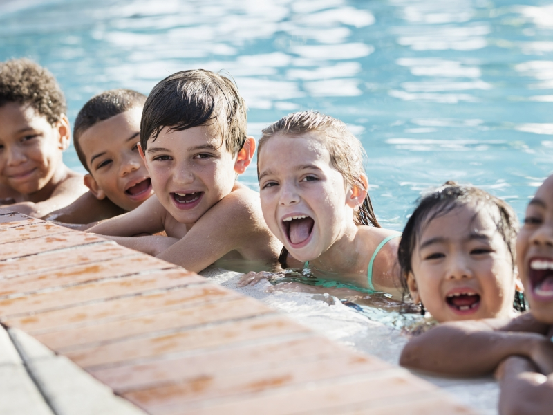 Six young children laugh in a pool with their elbows resting on the pool's edge.