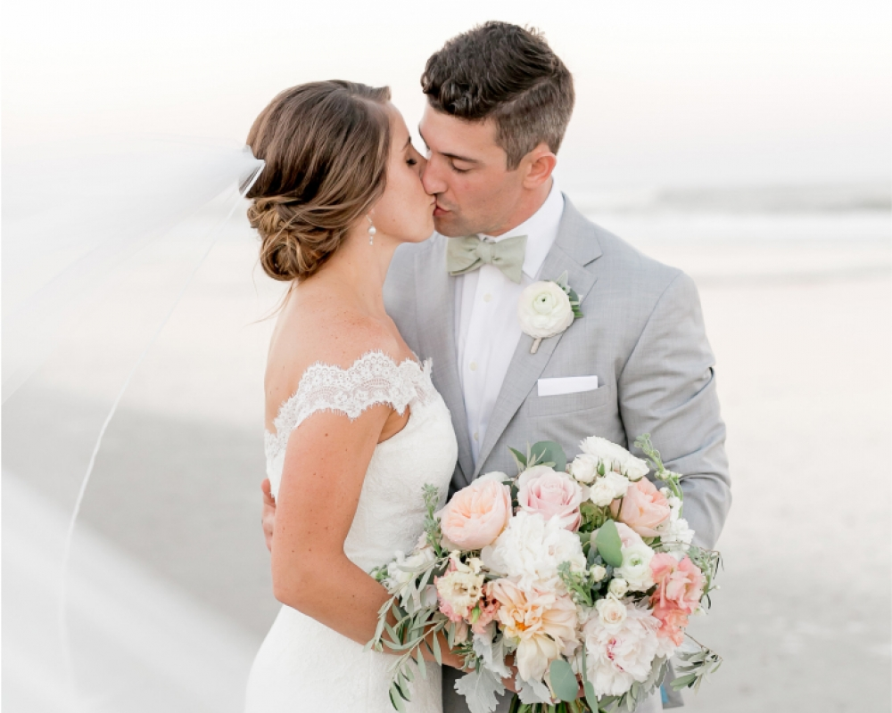 A bride and groom kiss on the beach while holding a bouquet of white and pink flowers.