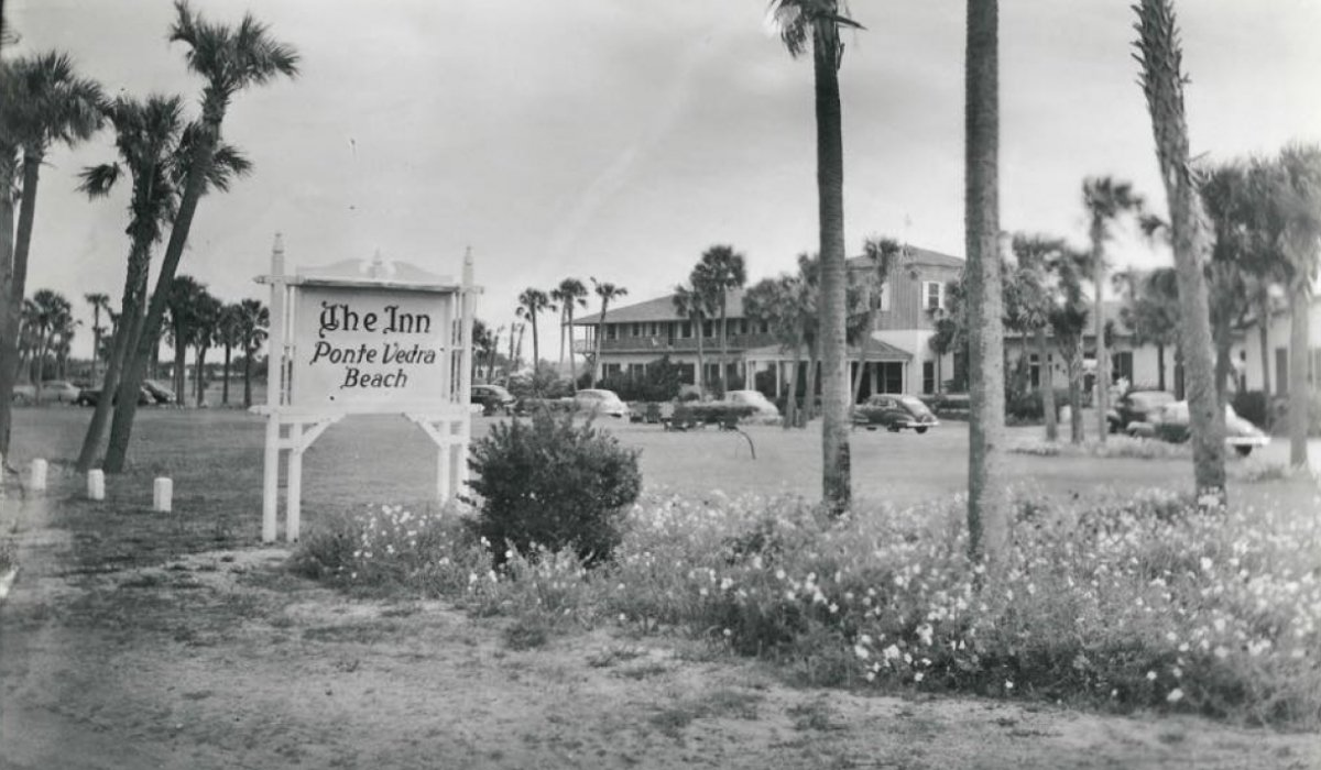 A black and white photo of palm trees and the Historic Inn building in the early days of Ponte Vedra Inn & Club.