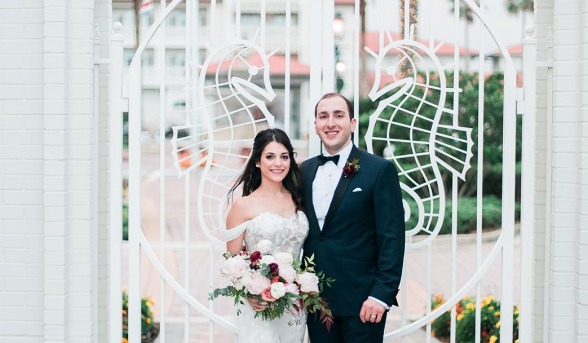 A bride and groom stand in front of a white gate decorated with seahorses, with Ponte Vedra Inn & Club in the background.