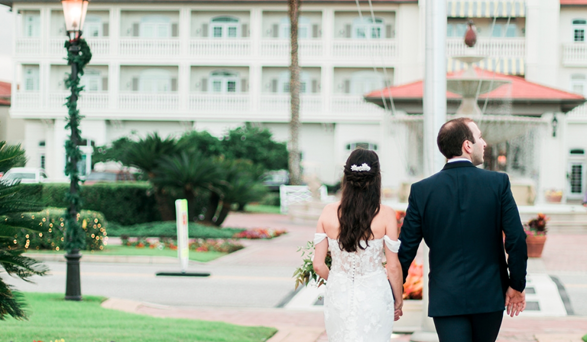 A bride and groom walk down a stone pathway towards the Historic Inn Building at Ponte Vedra Inn & Club