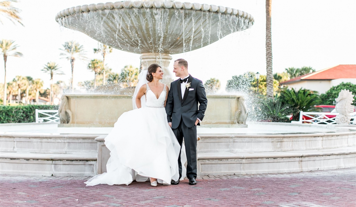 A smiling bride and groom stand in front of the famous fountain at Ponte Vedra Inn & Club.