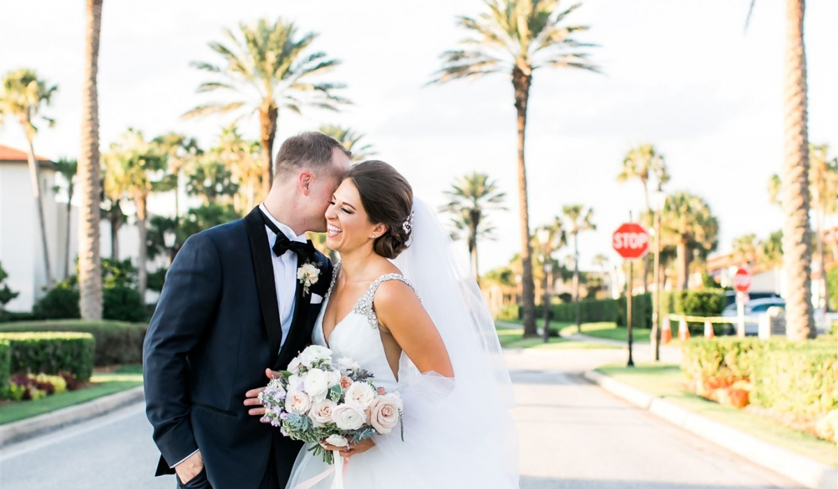 A bride and groom smile as they stand the street under palm trees at Ponte Vedra Inn & Club.