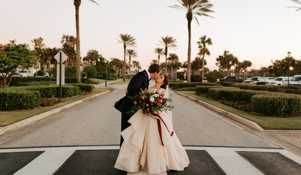 A bride and groom kiss in the street framed by palm trees at Ponte Vedra Inn & Club.