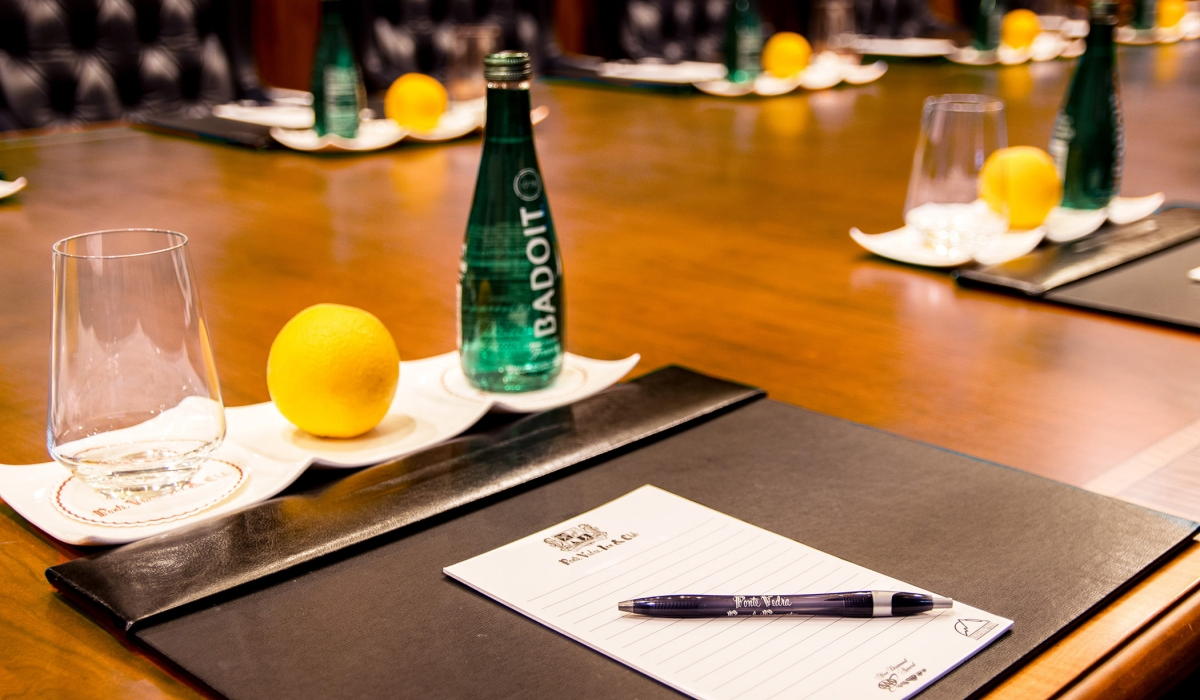 Close up of a notepad and pen, glass, lemon and carbonated water on a meeting table