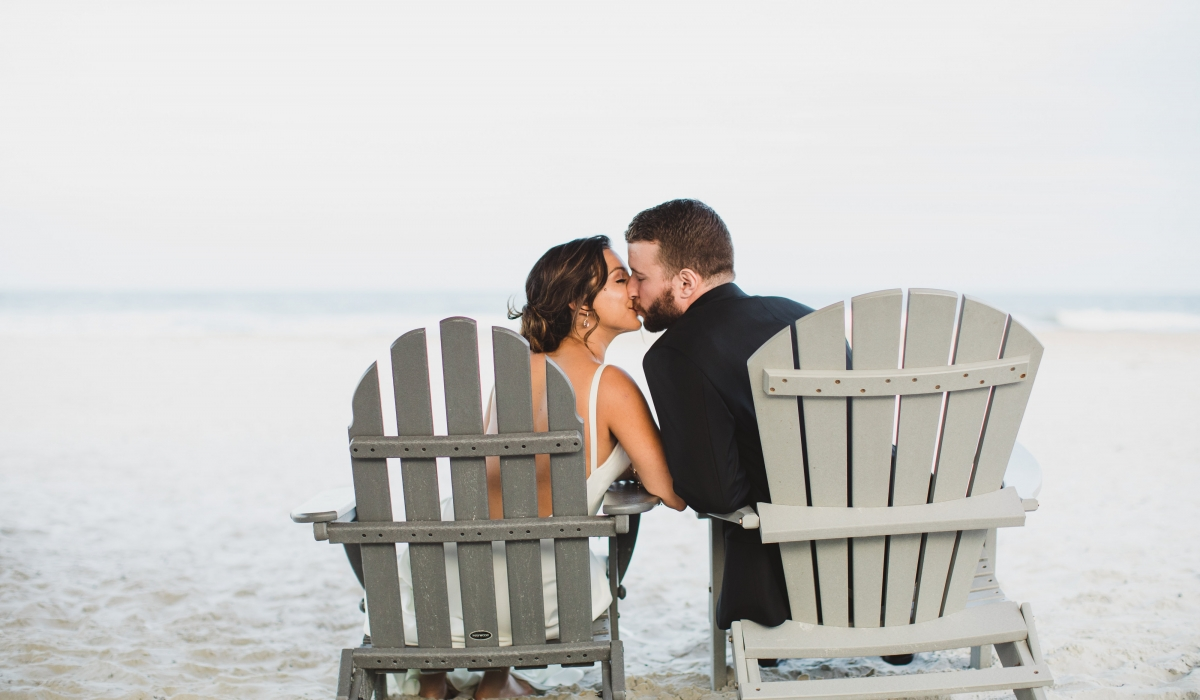 A bride and groom kiss as they sit in separate Adirondack chairs on the beach at Ponte Vedra Inn & Club.