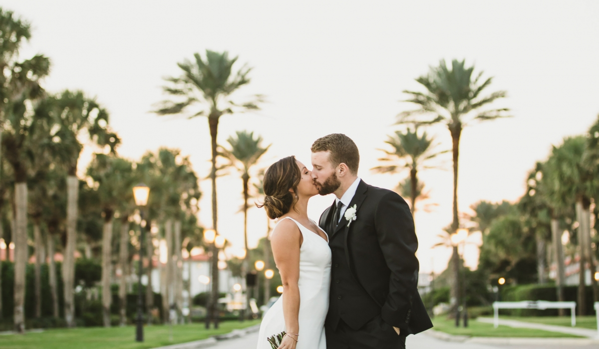 Framed by palms, a bride at groom kiss at Ponte Vedra Inn & Club.