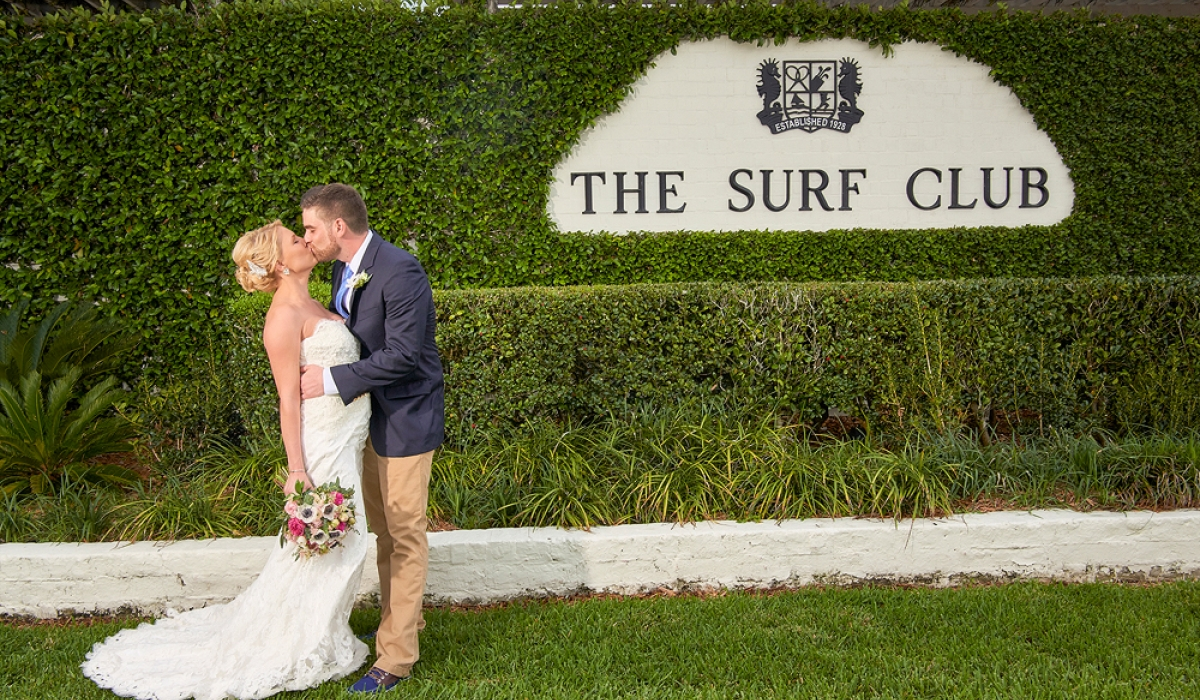 A brdige and groom kiss in front of a sign reading The Surf Club surrounded by greenery at Ponte Vedra Inn & Club.