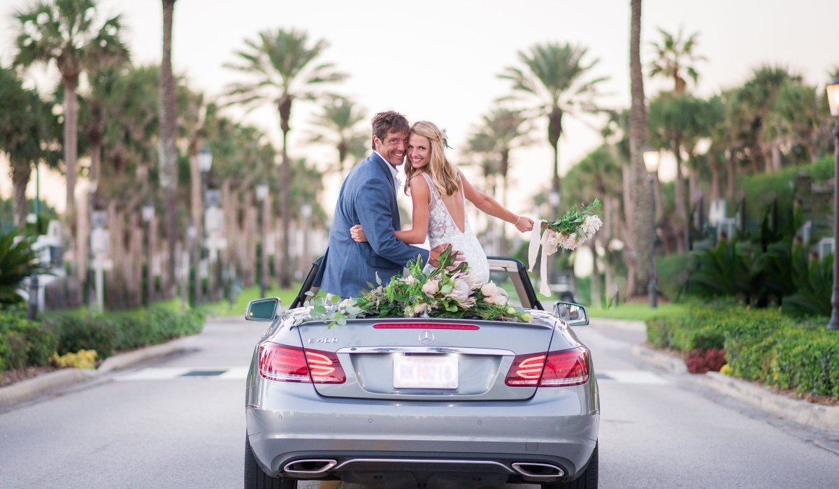 A bride and groom sit on the back of a Mercedes convertible looking behind them and smiling with a palm tree-lined street in the background.