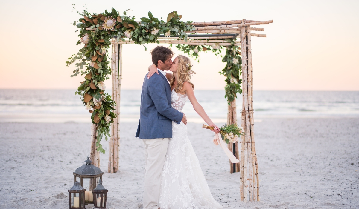 A bride and groom kiss under an arbor on the beach at Ponte Vedra Inn & Club.