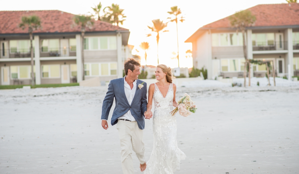A bride and groom walk hand in hand on the beach as the sun sets behind Ponte Vedra Inn & Club.
