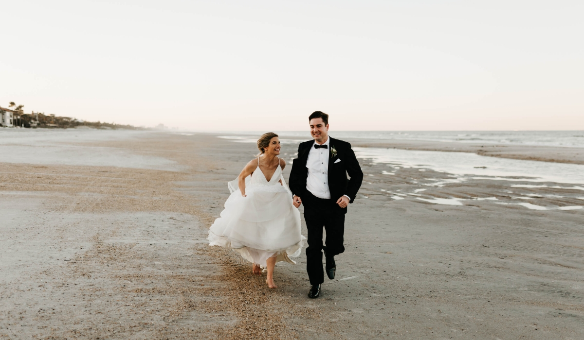 A bride and groom run along the beach at Ponte Vedra Inn & Club.