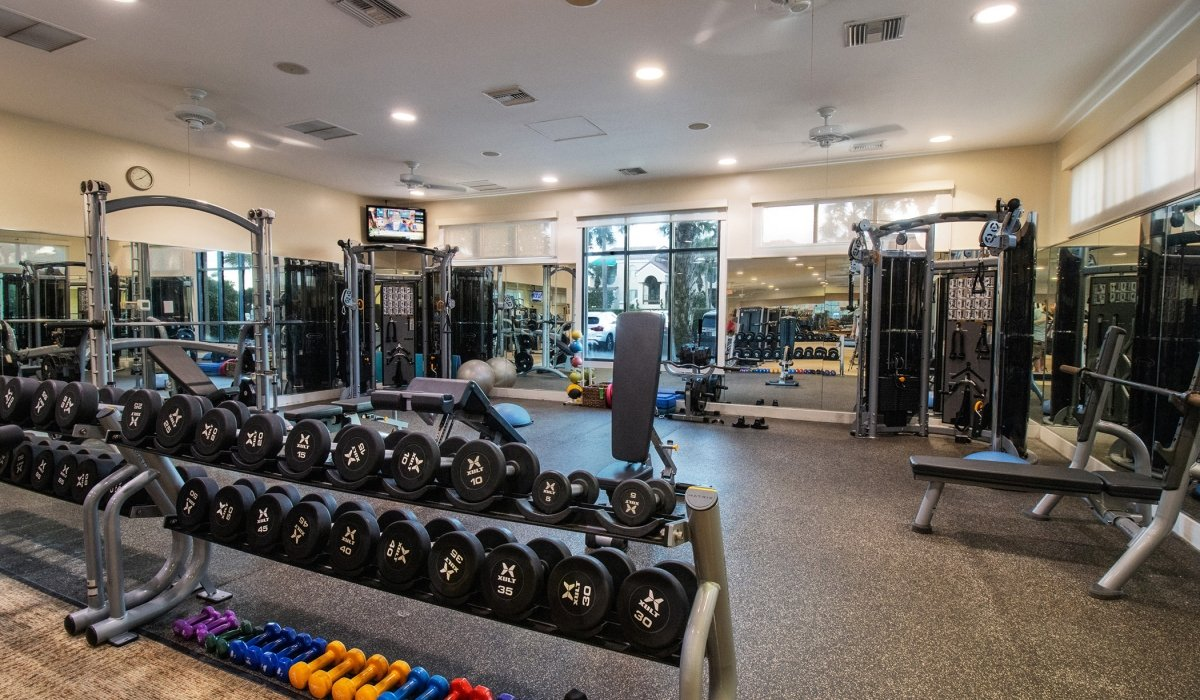 Fitness facility with a rack of dumbbells in the forefront