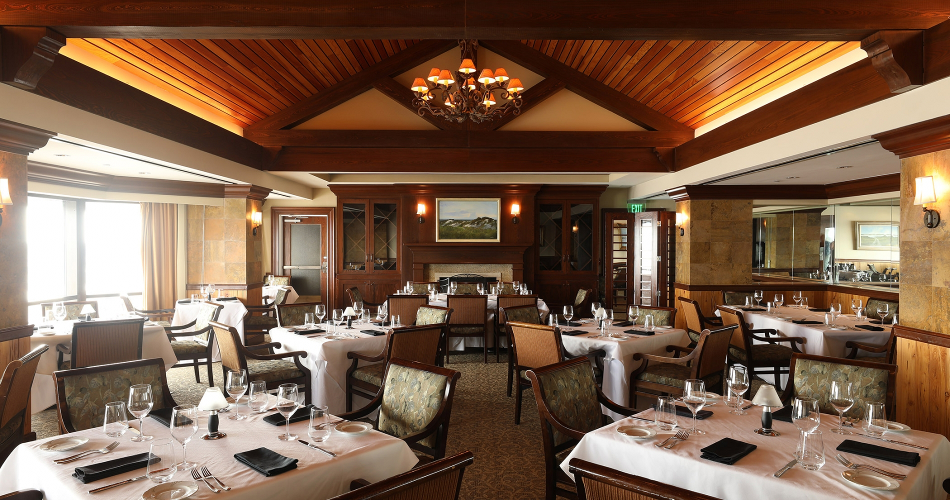 Set tables in a restaurant with a high, wood paneled ceiling