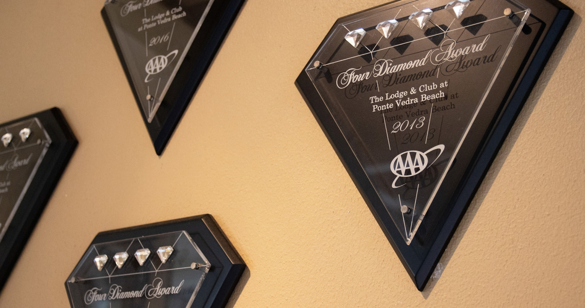 Four AAA Four Diamond awards hanging on a wall