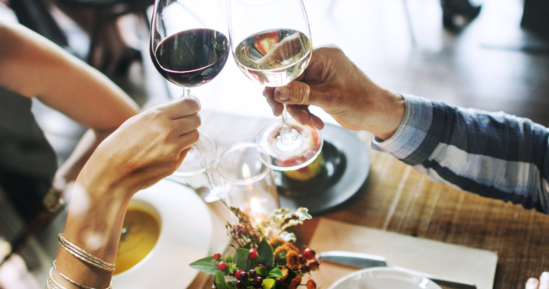 A woman's hand holding a glass of red wine and a man's hand holding a glass of white wine cheers over a wooden table set with white dishes.