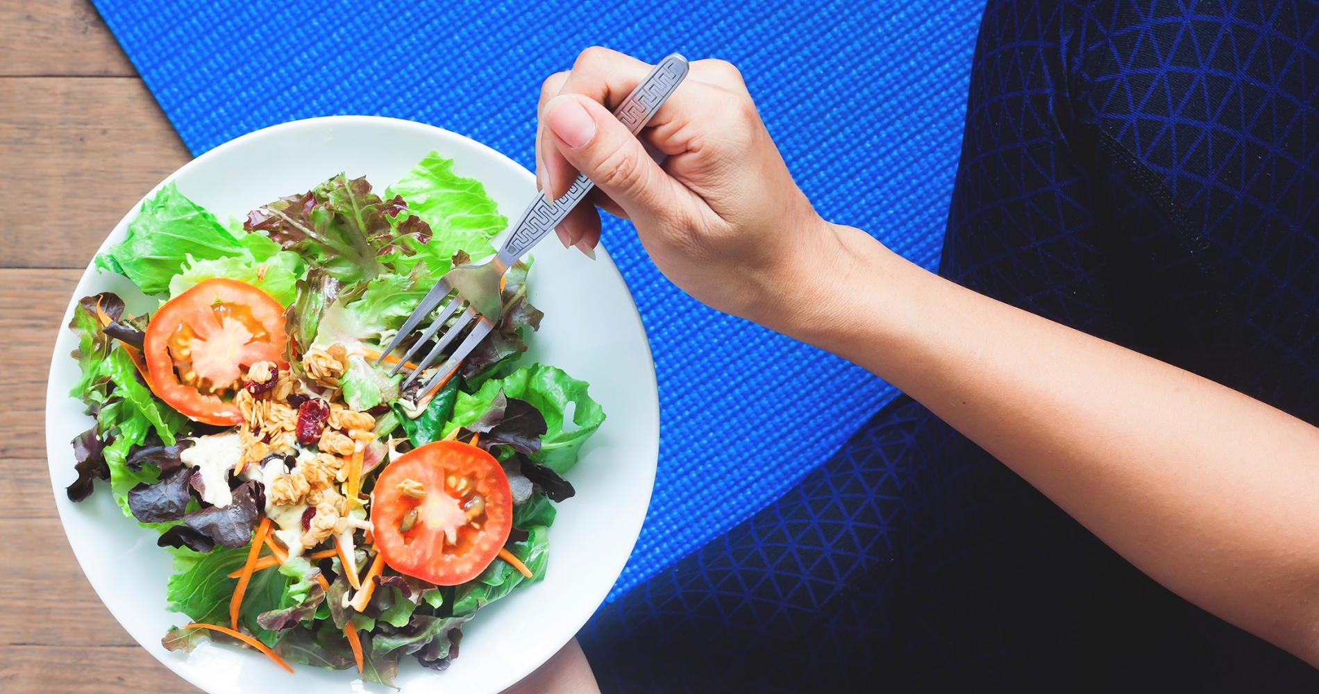 An arm holding a fork over a white bowl filled with salad greens and tomatoes.