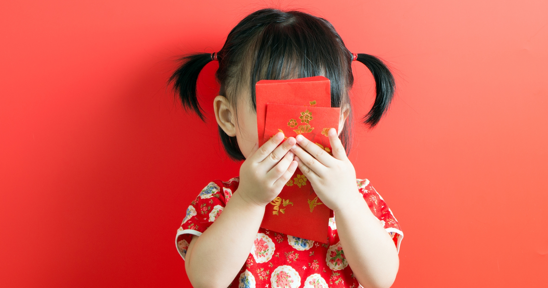 A girl with pigtails stands in front of a red background folding red cards embossed with gold print in front of her face.