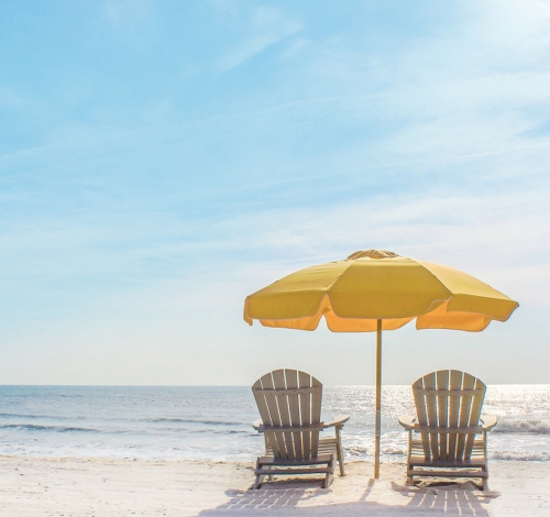 two beach chairs with yellow umbrella along ocean coast
